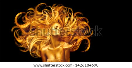 Gold Woman. Beauty fashion model girl with Golden make up, and Long hair pointing hand on black background. Gold glowing skin and fluttering hair. Metallic, glance Fashion art portrait, Hairstyle