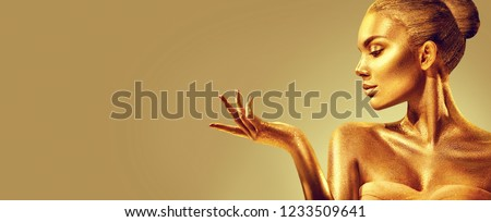Gold Woman skin. Christmas Beauty fashion model girl with Golden make-up, hair and jewellery on gold background. Pointing hand, proposing products, sales. Metallic glance Fashion art portrait, glamour #1233509641