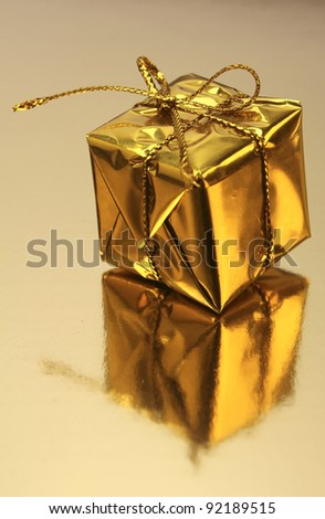 Gold wrapped gift on a golden background