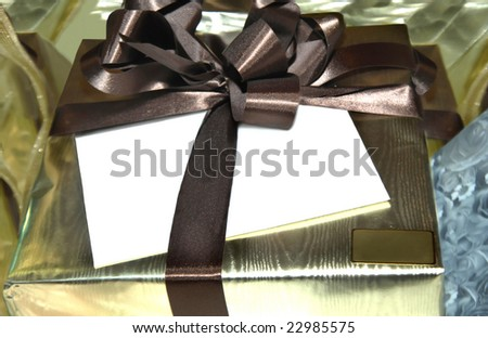 Gold wrapped package is tied with brown ribbon.  Blank white envelope sits under ribbon.  Small square can be personalized.