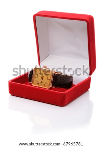 Gold wrist watch in a red velvet box on white background