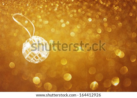 golden abstract bokeh lights and miniature glitter ball. party or music concept.