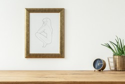 Golden alarm clock and a aloe in a basket on a shelf and a line drawing art in a frame on a white empty wall