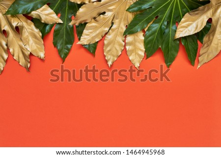 Golden and green tropical leaves on bright coral color backdrop. Minimal summer exotic concept with copy space. Copy space, top view.
