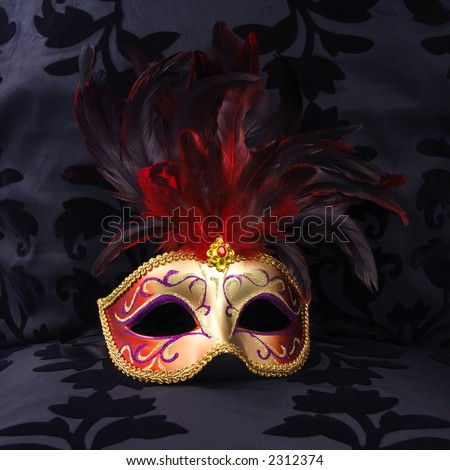 golden and red colored mask at a black velvet seat  (Venice, Italy)