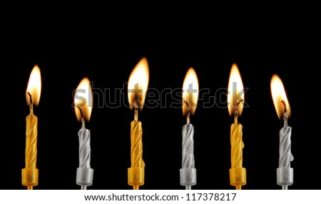 Golden and silver burning candles on black background