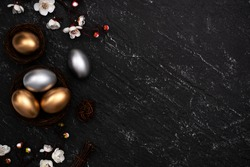 Golden and silver Easter eggs with plum blossom flower on dark black slate table background.