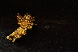 Golden angel on black shiny background, yellow glitter toy, Christmas decoration, place for text