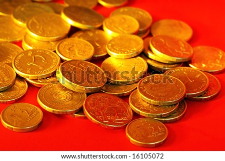 Golden Australian one and two dollar coins, scattered on red background.