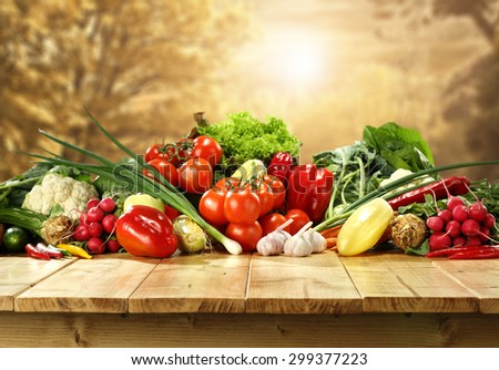 golden autumn background trees and few fresh vegetables on top of table
