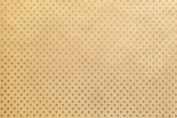 Golden background from metal foil paper with a pattern of sparkling stars closeup. Texture of yellow metallized wrapping holiday paper surface.