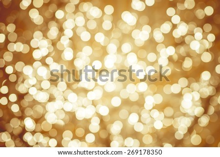 Golden background with natural bokeh defocused sparkling lights. Colorful metallic texture with twinkling lights. Bright and vivid colors