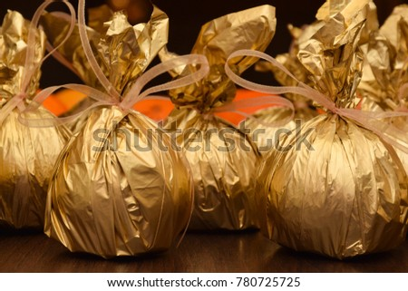 Golden bags with heartfelt wishes. Mandarins and notes with wishes are wrapped in gold paper, orange mandarins in the background..