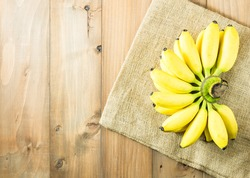 golden banana on gunny sack cloth and wooden table, top view, copy space