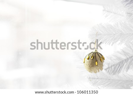 Golden bauble hanging on white Christmas Three with winter scene behind the window