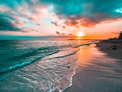 Golden beach sunset on a tropical island. Orange, teal, pink tones