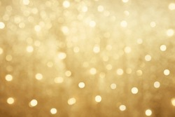 Golden beautiful blurred bokeh background with copy space. Holiday texture. Wallpaper. Glitter light spots on golden background, defocused