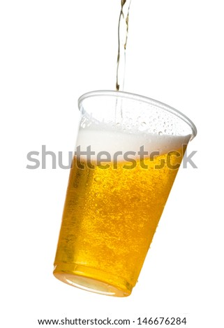 Golden beer, ale or lager in a tilting plastic disposable cup or glass with beer being poured and spilling over edge of pint glass