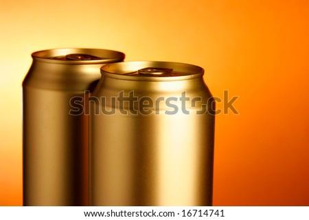 Golden beer cans close-up over orange background