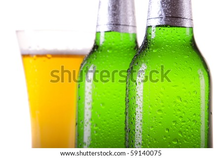 Golden beer in mug and perfect green bottle on white background