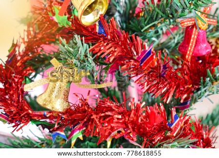 Golden bell hanging on a Christmas tree with a ribbon and golden light as a background. Ideas for Christmas. select focus. close up.