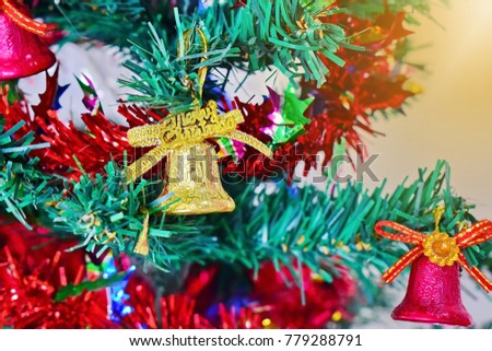 Golden bell hanging on a Christmas tree with a ribbon and golden light as a background. Ideas for Christmas. select focus. close up. #779288791