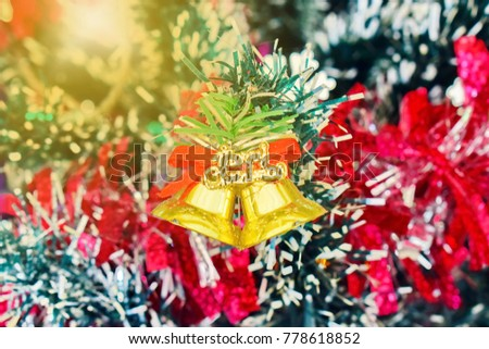 Golden bell with red ribbon hanging on Christmas tree with ribbon and golden light as background. Ideas for Christmas. select focus. close up. #778618852