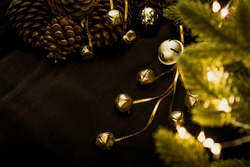 Golden bells on a black background with bright lights of a Christmas garland. Christmas toys lie with pine cones and green fir branches. Bright lights of garlands on the branches of a Christmas tree.