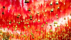 Golden bells with greeting lucky word on red ribbon at Kalighat Kali Mandir Temple Kolkata. Pilgrims people wish and hang it on rope for pray. Merry christmas happy new year concept background texture
