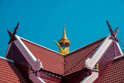 Golden bird sculpture on the roof at Trilak Cemetery in Lampang Thailand.  Thai - northern roof style with blue sky.