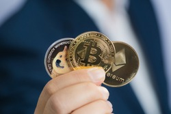 Golden bitcoin coin Dogecoin DOGE, Ethereum ETH group included with Cryptocurrency on hand business man wearing a blue suit. Filed and put and give to me. Close up and Macro photography concept.