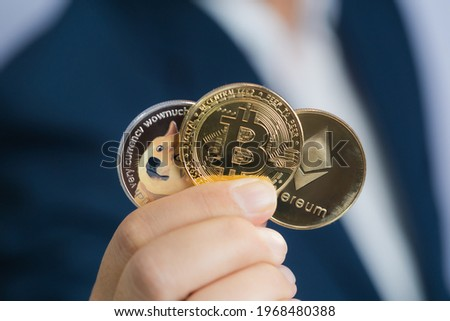 Golden bitcoin coin Dogecoin DOGE, Ethereum ETH group included with Cryptocurrency on hand business man wearing a blue suit. Filed and put and give to me. Close up and Macro photography concept. Сток-фото ©