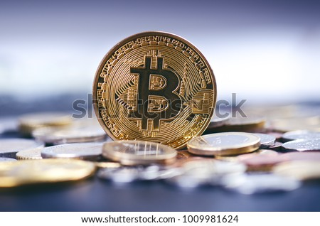 Golden bitcoin coins on a dark background with euro coins.  Virtual currency. Crypto currency. New virtual money. Lens flare