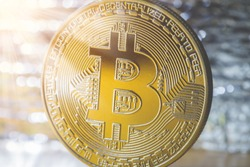 Golden Bitcoin in a ray of light on a silver background. Close up