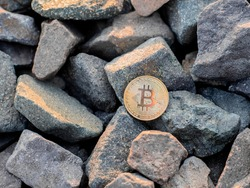 golden bitcoin on the stones. yellow btc on the rocks. gold coin beautiful. Stock photo. Crypto mining currency, miner