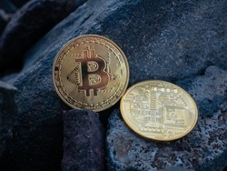 golden bitcoins on the stones. yellow btc on the rocks. gold coin beautiful. Stock photo. Crypto mining currency, miner