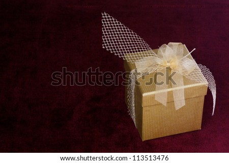 Golden box wrapped as a present on a bordeaux velvet cloth