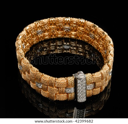 Golden bracelet with diamonds over black background