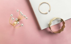 Golden bracelet with pearls and golden zigzag shape cuff on pink and white paper background