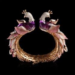 Golden bracelet with pink gem stones (Spinel) and Diamonds on reflective black background.