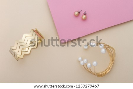 Golden bracelets and earrings on beige and pink background - Golden and pearls bracelet and golden cuff with pair of earrings on pink and beige