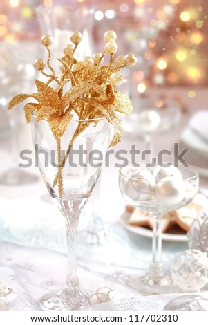 Golden branch on Christmas table. Place setting in white and golden tone.