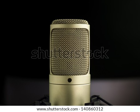 golden broadcast voice microphone on dark background - close-up shoot