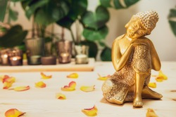 Golden bronze Buddha decorative statuette with flower petals on the wooden table with burnig candles, monstera plant background. Meditation ritual, Spirituality, buddhism and religion. Selective focus