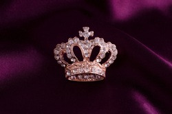 golden brooch crown isolated on white silk