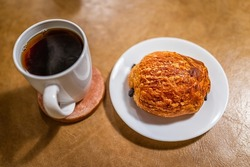 Golden brown baked pastry croissant on plates with flaky crusts and chocolate filling by cup of chicory coffee substitute morning breakfast