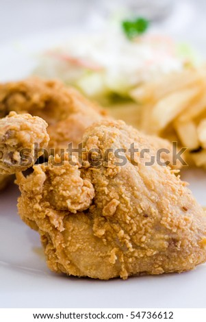 Golden brown deep fried chicken being served on a white plate with fries and salad.