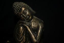 golden buddha figure, medium shot, serene gaze, head resting on his knee resting
