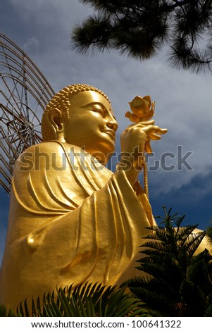 Golden Buddha holding the golden lotus from the up angle