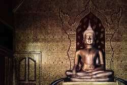 golden buddha image with ancient thai painting style as background at Wat Pipat Mongkol temple, Sukhothai, Thailand